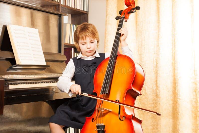 校服的美丽的女孩在大提琴使用 免版税库存图片