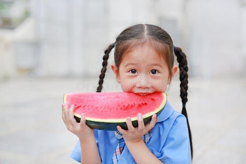 校服的逗人喜爱的矮小的亚裔儿童女孩喜欢吃新鲜的切的西瓜 免版税图库摄影