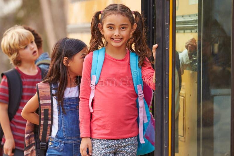校车队列的前面的小学女孩 库存图片