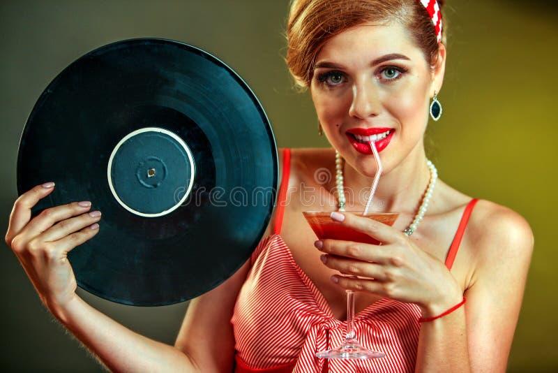 样式的女孩保留唱片和饮料马蒂尼鸡尾酒鸡尾酒 免版税图库摄影