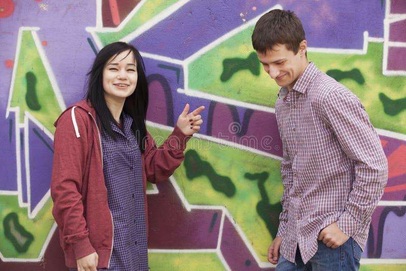 样式青少年的夫妇临近街道画背景。 图库摄影
