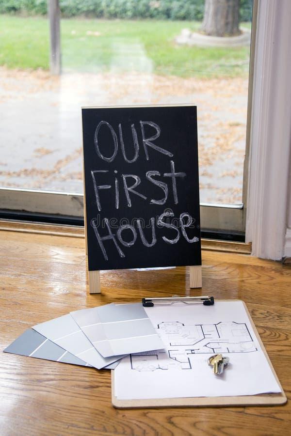 绘样片并且安置在地板上的计划与第一个房子标志 免版税库存照片