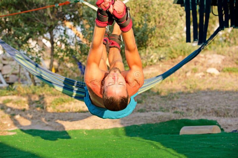 核心的,瑜伽摇摆,亭亭玉立的年轻人瑜伽治疗被束缚对在地面,人开发的耐力上的四个板条 免版税库存图片