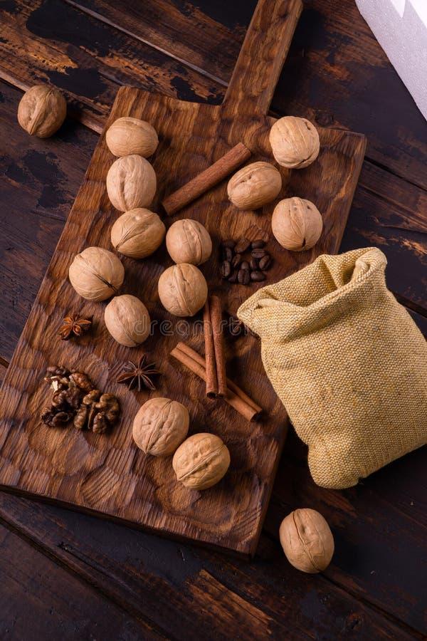 核桃、桂香、八角、咖啡豆和小袋子在木切板 坚果和香料在桌上 ?? 图库摄影