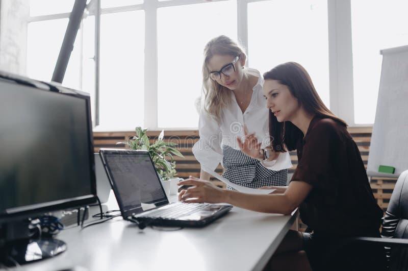 根据办公室dreskod打扮的两年轻美女与膝上型计算机一起工作在光的书桌 免版税库存图片