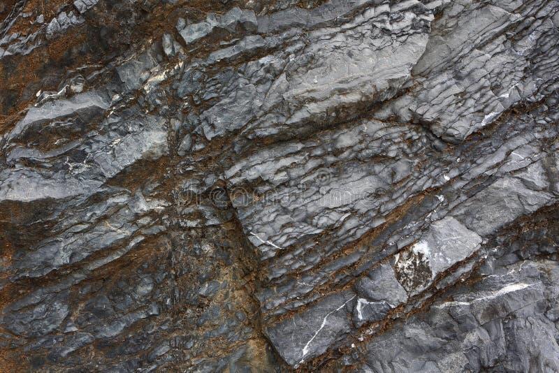根据岩石纹理的背景  与倾斜的层数和镇压的黑和棕色石头 图库摄影