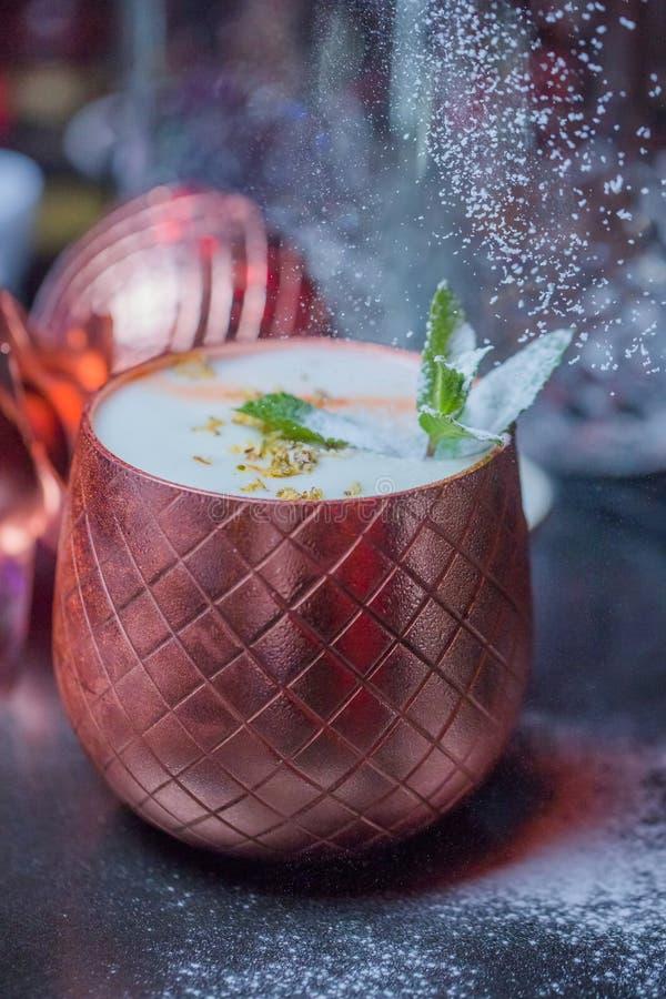 根据椰奶-与白色巧克力和椰子削片的为装边的玻璃的鸡尾酒 免版税库存照片