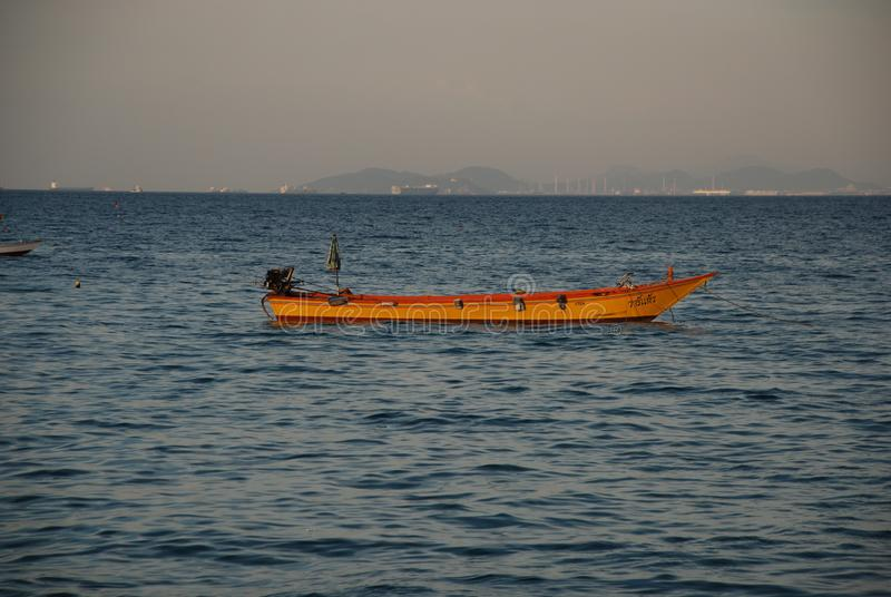 根据落日的一条孤立小船在芭达亚港  库存照片