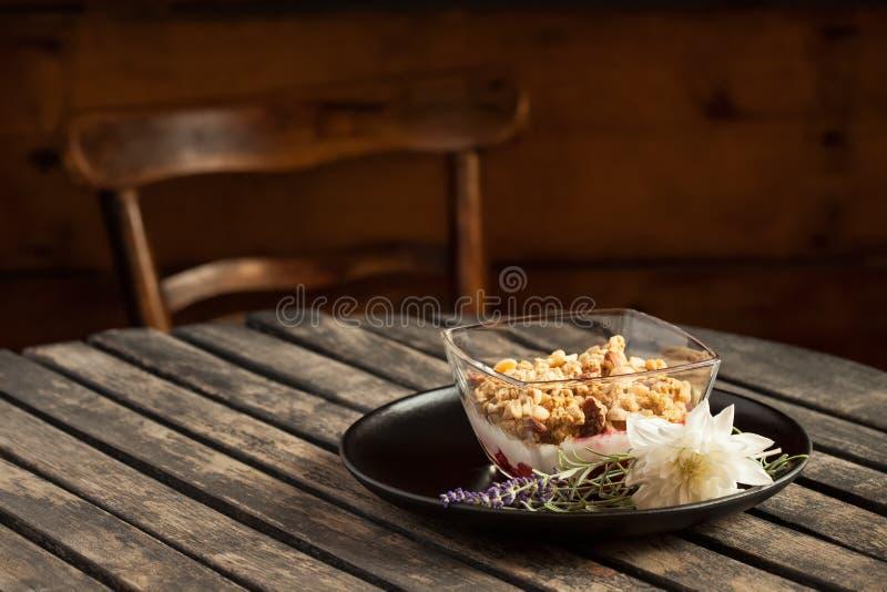 格兰诺拉麦片、鲜美点心用希腊酸奶和混杂的莓果在木桌上 免版税图库摄影
