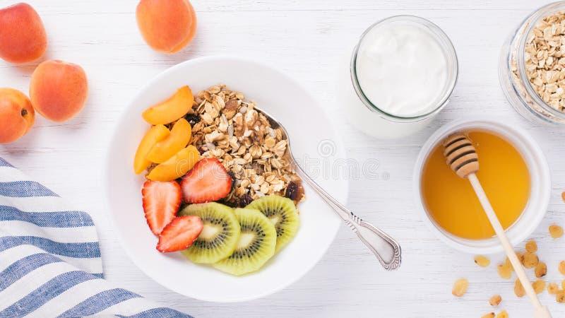格兰诺拉麦片和酸奶在桌上 免版税库存图片