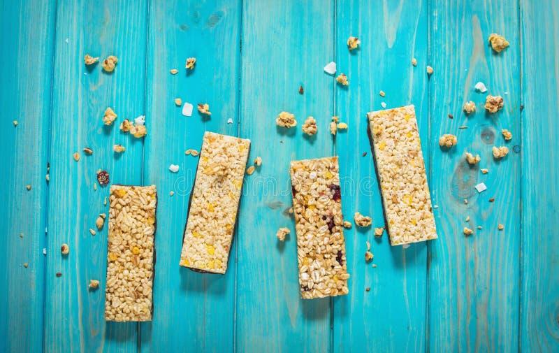 格兰诺拉麦片强身糕用燕麦粥,杏仁,干蔓越桔 在蓝色木背景的健康快餐 免版税库存图片