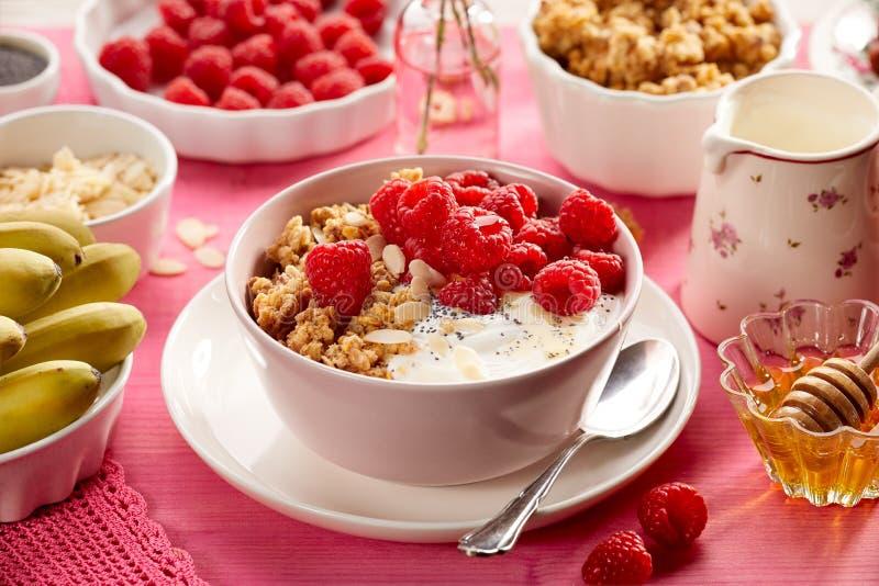 格兰诺拉麦片用自然酸奶、新鲜的莓、蜂蜜、杏仁剥落和罂粟种子在一个陶瓷碗在一张桃红色木桌上, 图库摄影
