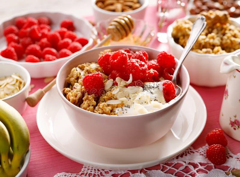 格兰诺拉麦片用自然酸奶、新鲜的莓、蜂蜜、杏仁剥落和罂粟种子在一个陶瓷碗在一张桃红色木桌上, 库存图片