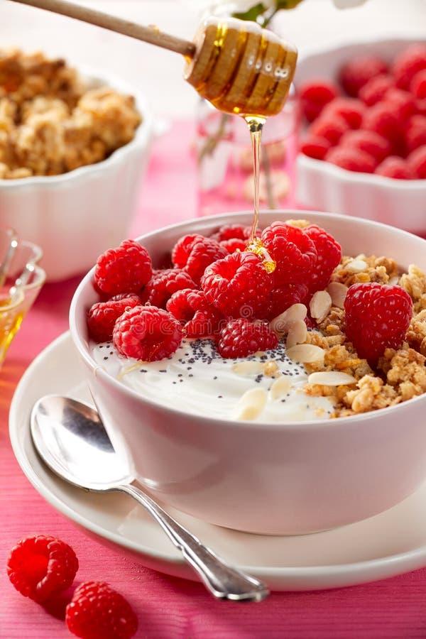 格兰诺拉麦片用自然酸奶、新鲜的莓、蜂蜜、杏仁剥落和罂粟种子在一个陶瓷碗在一张桃红色木桌上, 免版税库存图片