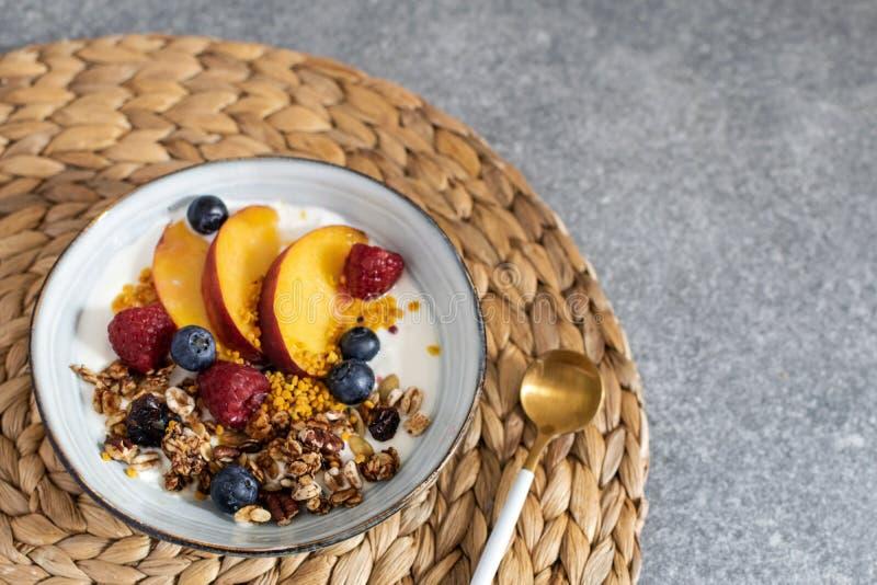 格兰诺拉麦片用酸奶新鲜的桃子,蓝莓,在桌上的莓-健康早餐 库存照片