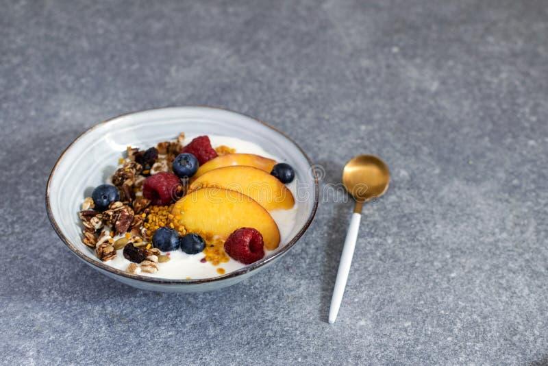 格兰诺拉麦片用酸奶新鲜的桃子,蓝莓,在桌上的莓-健康早餐 免版税库存图片