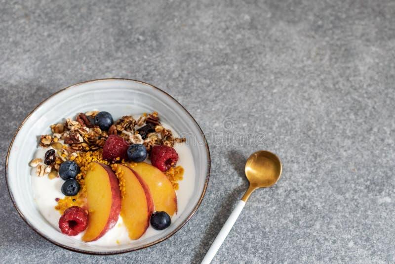 格兰诺拉麦片用酸奶新鲜的桃子,蓝莓,在桌上的莓-健康早餐 免版税库存照片