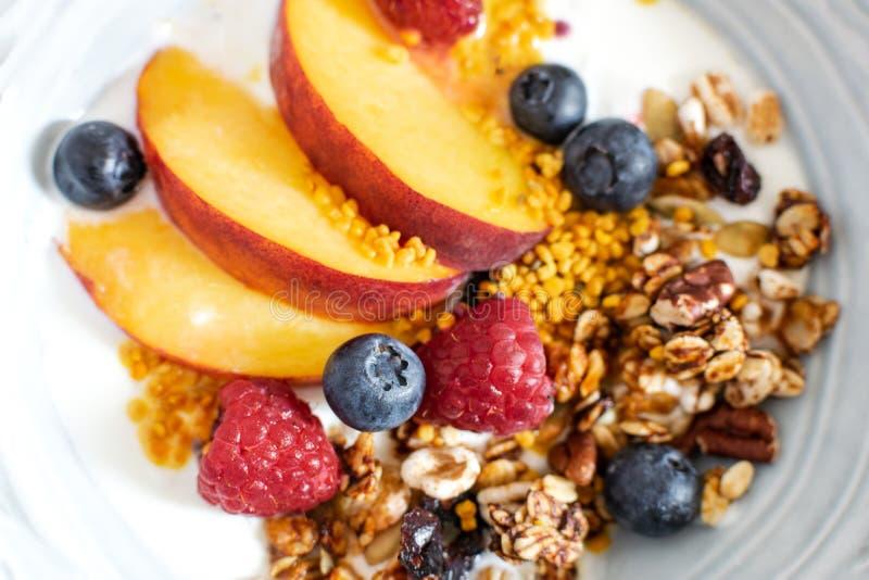 格兰诺拉麦片顶视图选择聚焦用希腊酸奶新鲜的桃子,蓝莓,在桌上的莓-健康早餐 图库摄影