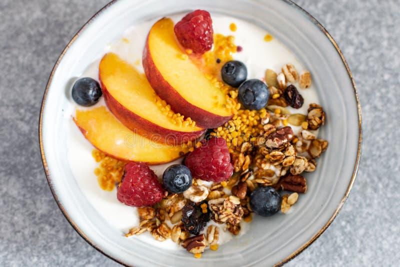 格兰诺拉麦片顶视图选择聚焦用希腊酸奶新鲜的桃子,蓝莓,在桌上的莓-健康早餐 库存照片