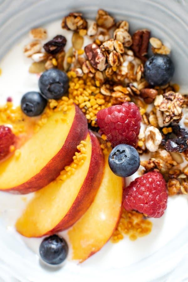 格兰诺拉麦片顶视图选择聚焦用希腊酸奶新鲜的桃子,蓝莓,在桌上的莓-健康早餐 免版税图库摄影