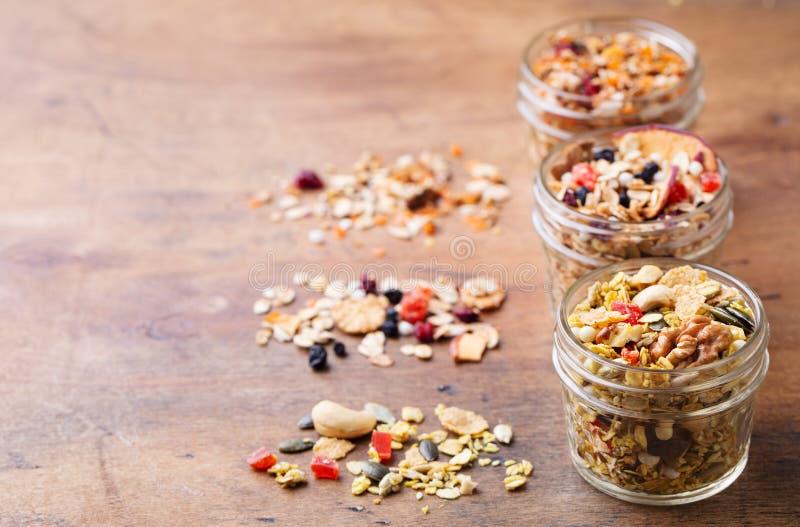 格兰诺拉麦片,在玻璃瓶子的muesli的分类 健康早餐有机燕麦用苹果、莓果和坚果 复制空间 库存图片