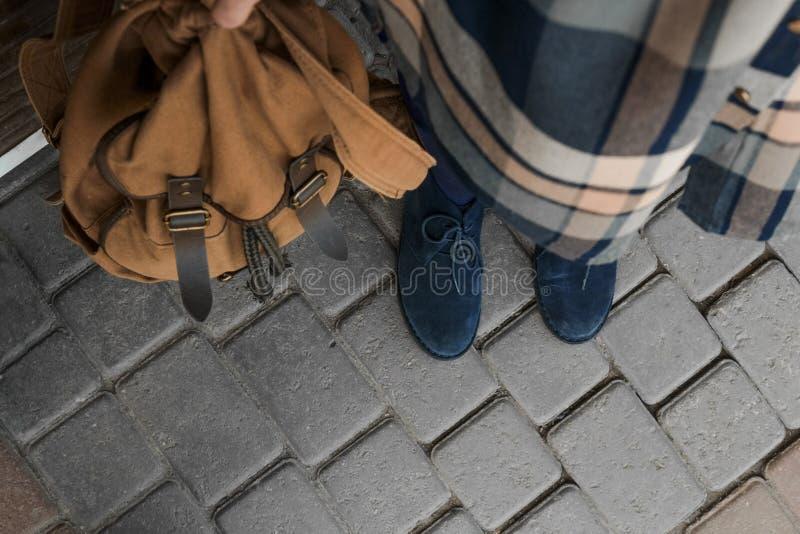 格子花呢上衣、蓝色起动和棕色背包 图库摄影
