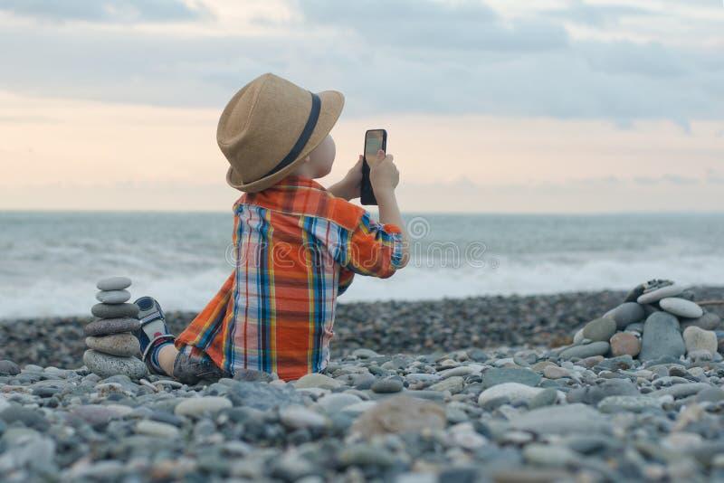 格子花呢上衣和帽子的小男孩坐海滩并且拍在智能手机的照片在海和天空背景 免版税库存照片