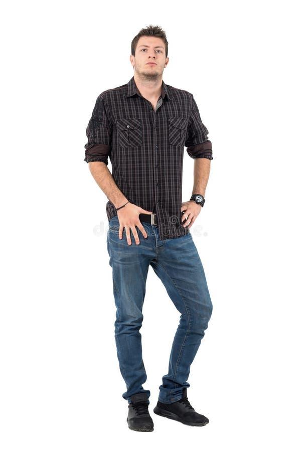格子花呢上衣和牛仔裤的确信的偶然人用在看照相机的传送带的手 图库摄影