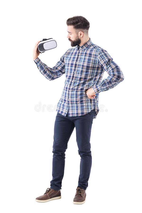 格子花呢上衣的怀疑有胡子的年轻行家审查虚拟现实玻璃的 库存图片