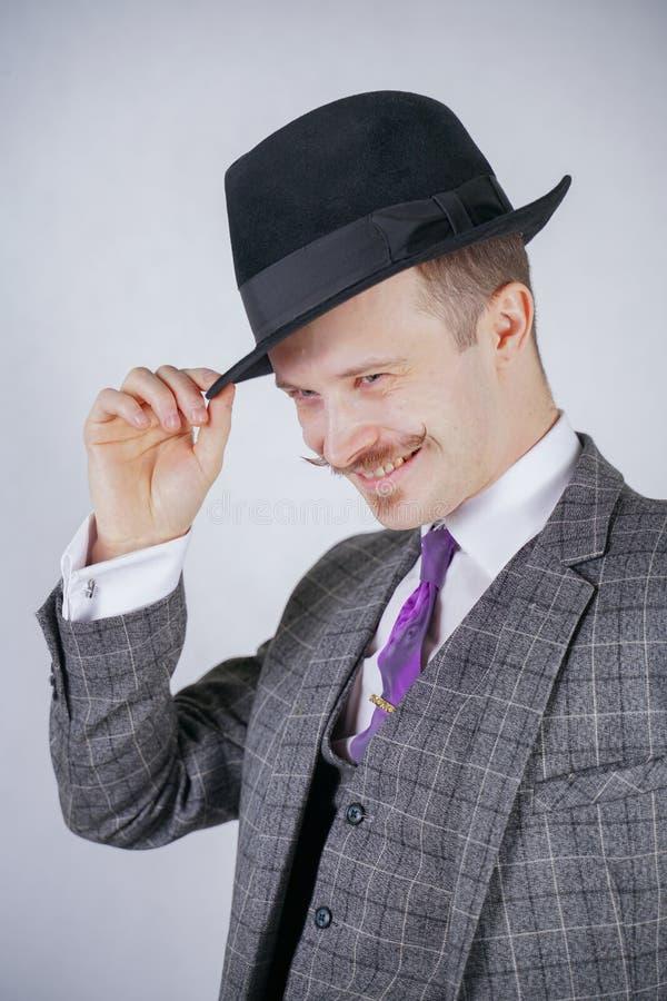 格子花呢披肩减速火箭的西装和葡萄酒高顶丝质礼帽的时髦的年轻人在白色坚实背景在演播室 免版税库存图片