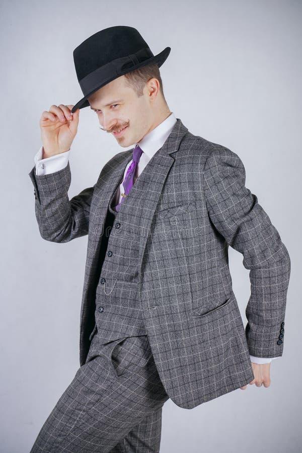格子花呢披肩减速火箭的西装和葡萄酒高顶丝质礼帽的时髦的年轻人在白色坚实背景在演播室 免版税库存照片