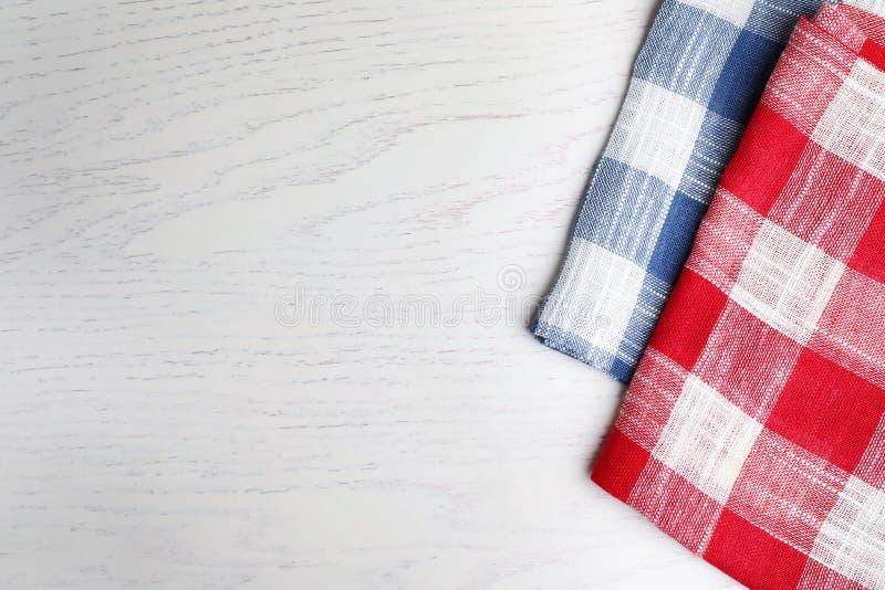 格子花呢披肩在白色木背景,顶视图的洗碗布 空间为 图库摄影