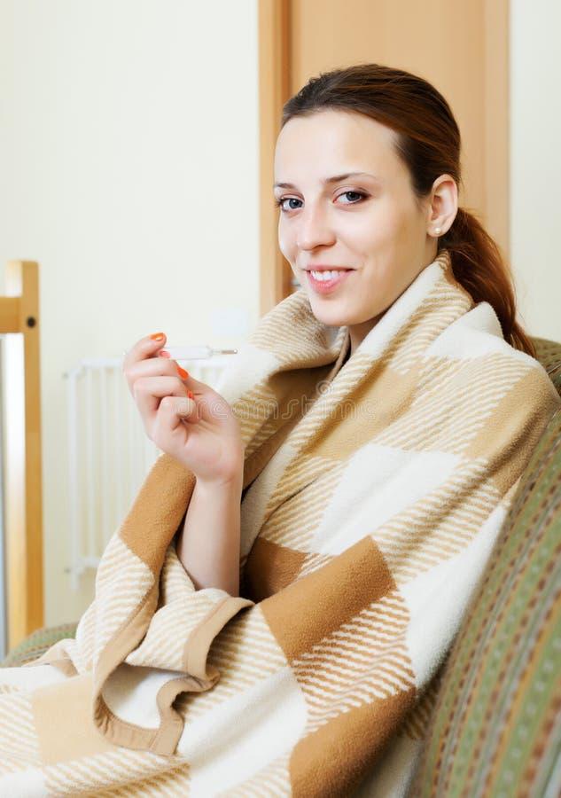 格子花呢披肩的微笑的妇女有温度计的 免版税库存照片