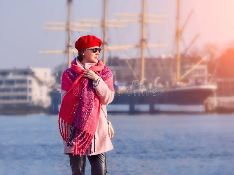 格子花呢披肩的美丽的白种人妇女走在河岸,生活方式画象的 免版税库存图片