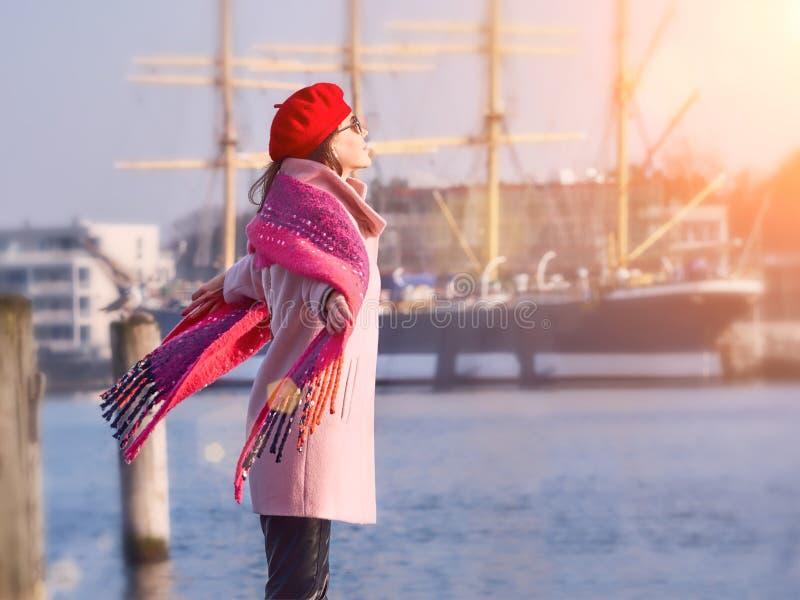 格子花呢披肩的美女走在河岸,春天太阳,好天气,生活方式画象的 免版税库存照片