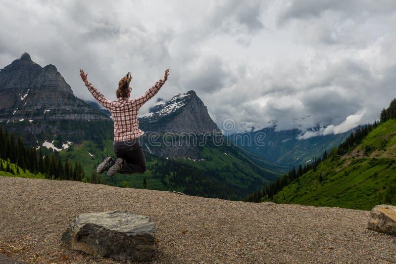 格子花呢披肩飞跃的妇女在蒙大拿罗基斯 免版税库存照片
