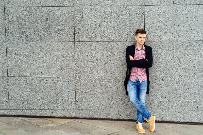 格子衬衫和夹克摆在的英俊的偶然年轻人 免版税库存照片