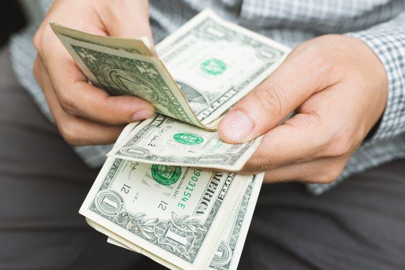 格子衬衫坐的手举行计数的接近的商人金钱 库存图片