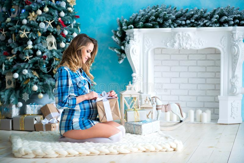 格子衬衫开放打开的礼物的美丽的年轻亭亭玉立的微笑的孕妇在圣诞树和壁炉附近 免版税库存图片