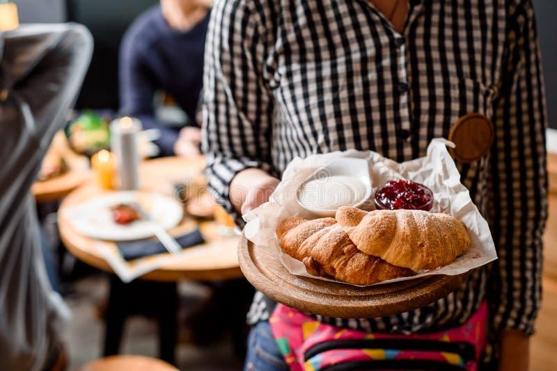 格子衬衫的女孩侍者拿着一个木盘子用新月形面包和果酱在餐馆内部 库存照片