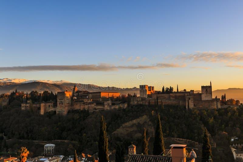 格拉纳达市,安达卢西亚,西班牙 阿尔罕布拉宫殿和堡垒的接近的图象有内华达山的背景的在日落 免版税库存照片