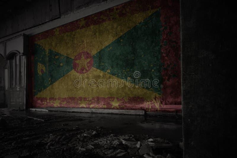 格林纳达的被绘的旗子在肮脏的老墙壁上的在一个被放弃的被破坏的房子里 图库摄影