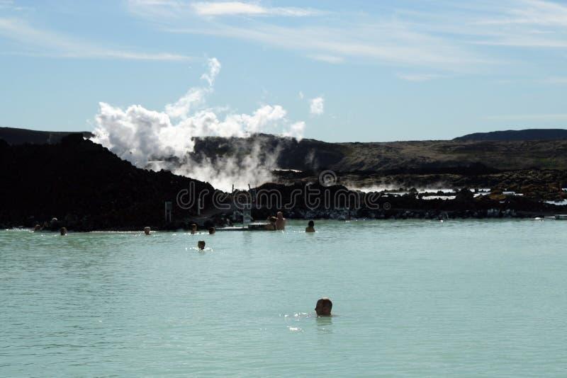 格林达维克蓝色盐水湖,冰岛- 7月27 2008年:放松在自然热的蓝色水池的人们 免版税库存图片