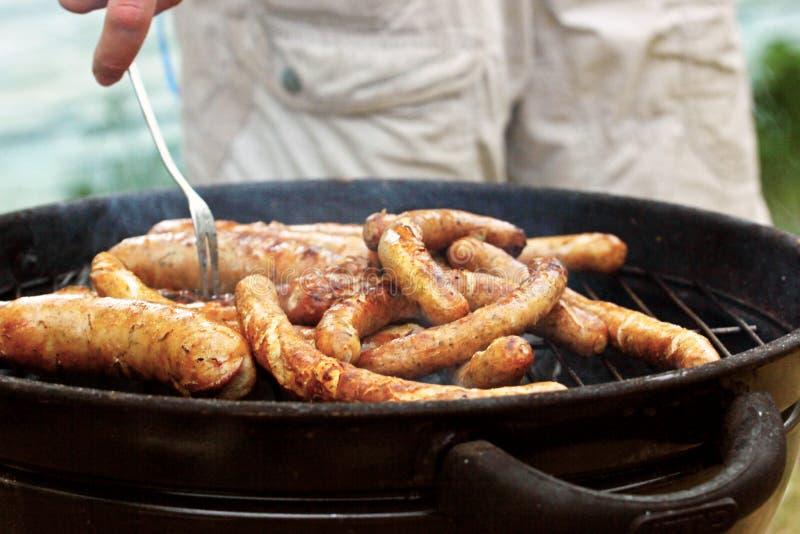格栅与一把叉子的油煎的香肠在自然本底 库存照片