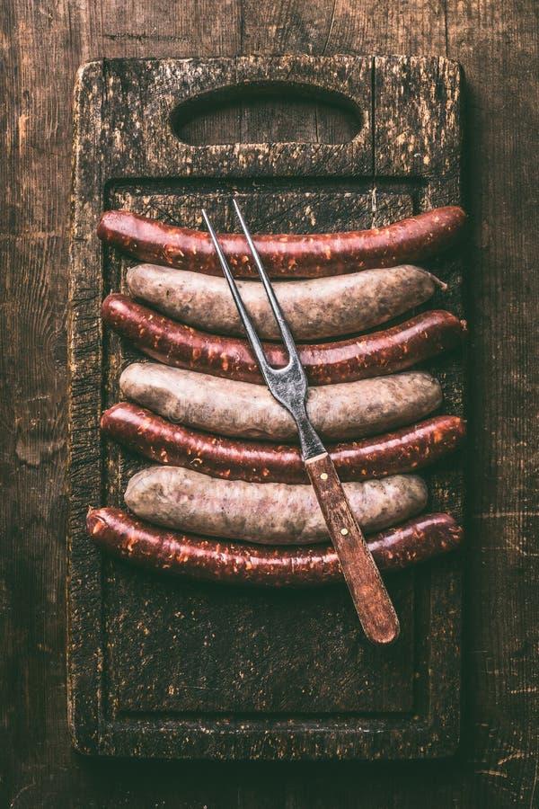 格栅或bbq的猪肉香肠在有集会叉子的黑暗的葡萄酒在土气木背景,顶视图的切板和餐巾 免版税库存照片