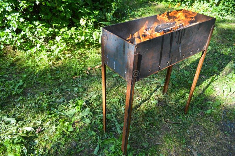 格栅烤肉野餐kebabs的大铁铸铁金属火盆与木燃烧注册与火的舌头的篝火 库存照片