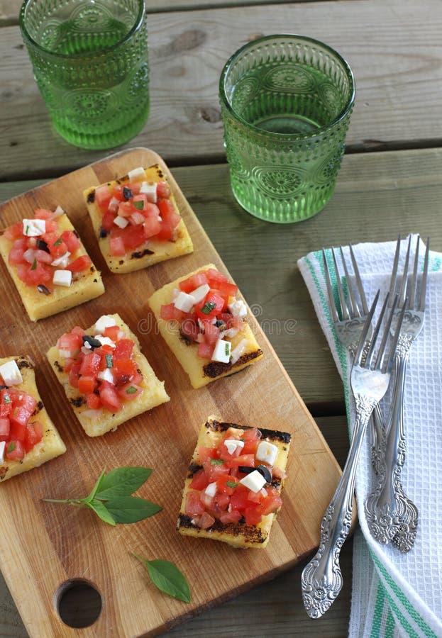 格栅玉米麦片粥用蕃茄、希脂乳和橄榄 库存照片