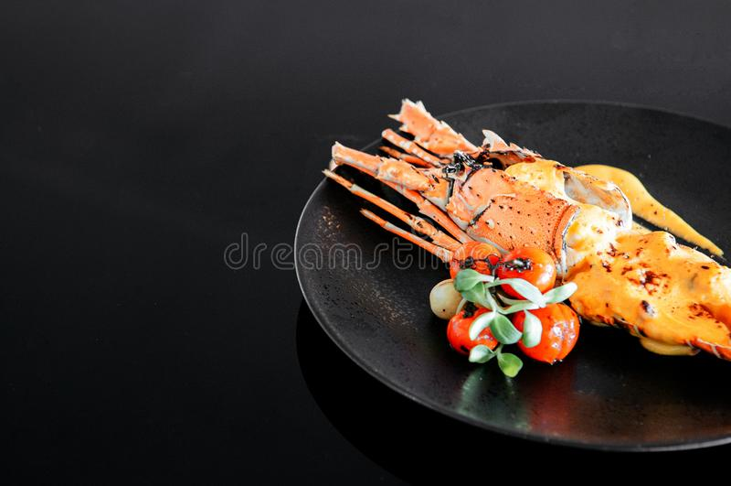 格栅被烘烤的亚洲彩虹龙虾用在黑色的盘子的乳脂状的黄油柠檬调味汁 免版税库存图片