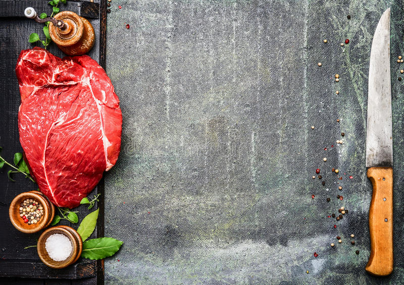 格栅BBQ的新鲜的生肉或烹调在厨房用桌上用香料和肉刀子 库存图片