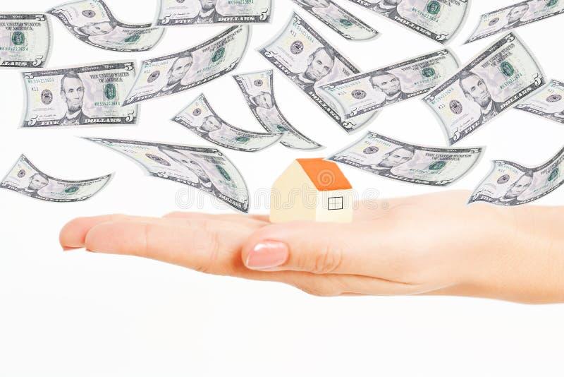 价格的演变在不动产产业的与在模型房子上的飞行金钱 免版税库存照片